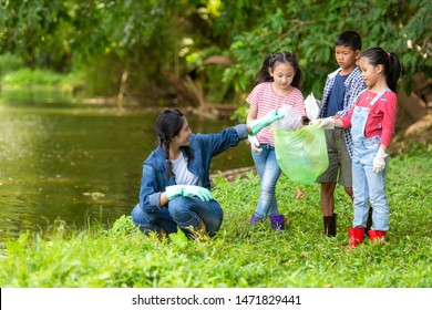 Group family asian children collecting garbage and plastic on the river to dumped into the trash for volunteer charity save environment.  Ecology earth Concept.