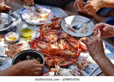 Group Family eating and peeling steamed big shrimp and spotted babylon, tray of many steamed shrimp, spotted babylon in pot, plate with cooked rice, shell shrimp on Thai newspaper, Party Thai style