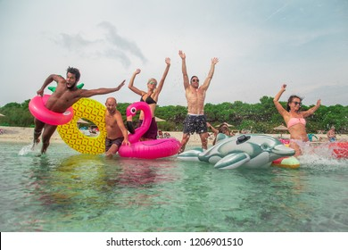 Group of family friends running madly into the sea with inflatable mattresses on summer beach.