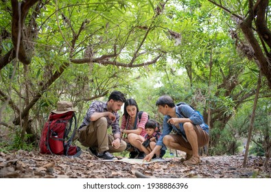 Group of family traveler, Caucacian father, Asian mother, daughter and grandfather squatting among forest trees looking at a hiking map placed on ground filled with dry leaves while hiking in forest.