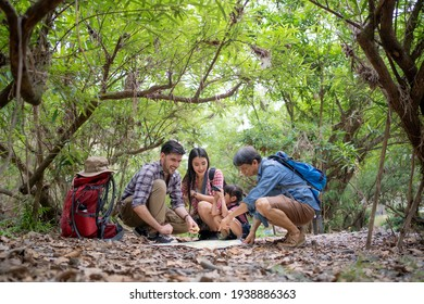 Group of family travelers squatting among forest trees consulting about the directions with a map placed on ground filled with dry leaves, a little girl looking through a binocular next to her mother.