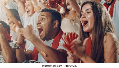 Group of fans cheer for their team victory on a stadium bleachers. They wear casual fan clothes.