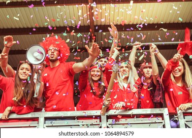 group of fans dressed in red color watching a sports event in the stands of a stadium