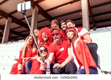 group of fans dressed in red color takes a selfie in the stands of a stadium during a sport event