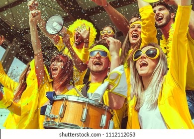 group of fans dressed in yellow color watching a sports event in the stands of a stadium