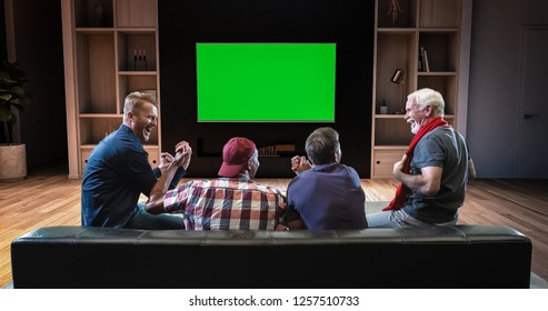 A group of fans is watching a TV and celebrating some joyful sports moment, sitting on the couch in the living room. The living room is made in 3D. TV is green screen for further editing.