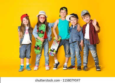 Group fashion cute preschooler kids friends together with skateboards is looking at camera on a yellow background. friendship, fashion, summer concept. Space for text.