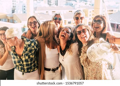 Group of female adult mixed generations people having fun together during party celebration - laughs and smile and cheerful caucasian women together hugging outdoor in friendship