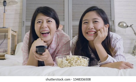Group of female best friends watching TV match and having fun together. lazy cute girls in pajamas lying on front in bed eating popcorn laughing at comedy on television hold control remote in bedroom