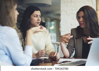 Group of female business partners having discussion about new project making creative solutions together.Skilled colleagues sharing ideas while brainstorming on informal meeting in coffee shop