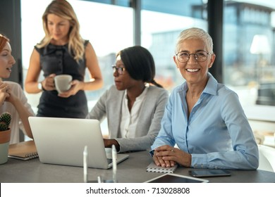 Group of female businesswomen working together on a laptop.