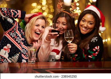 Group Of Female Friends Enjoying Christmas Drinks In Bar