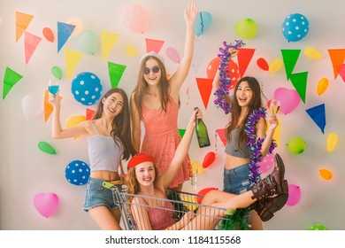 Group of female friends enjoying drinks in outdoor party. Cheerful young woman in santa hat and sitting in shopping cart at party with friend and colorful balloons, Party flags on background.