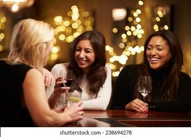 Group Of Female Friends Enjoying Evening Drinks In Bar