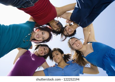 Group of female friends forming huddle against sky