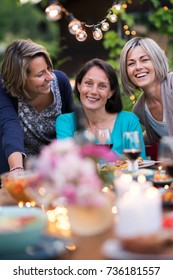 Group of  female friends gathered around a table in a garden on a summer evening to share a meal and have a good time together.Three women looking at the camera, they are in their forties