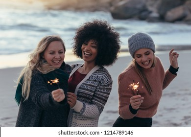 Group of female friends having fun with sparklers outdoors at the beach. Diverse group of young women celebrating new year's day at the beach.