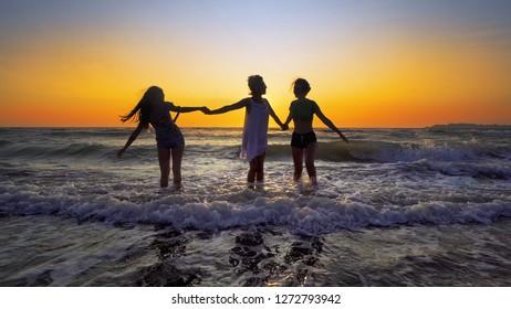 Group of female friends having fun splashing ocean waves on beach at sunset, cinematic steadicam SLOW MOTION