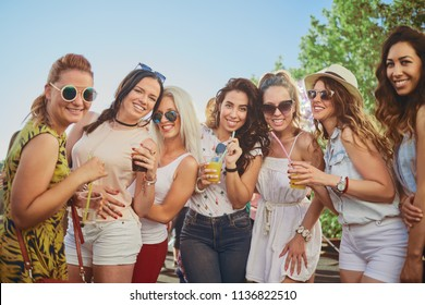 Group of female friends posing and having a good time at the outdoor party/music festival