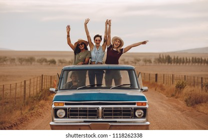 Group of female friends riding in pickup truck having fun on summer day. Three women standing at the back of pickup truck with their arms raises and smiling.