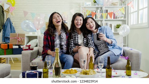 group of female friends sitting close in sofa hugging together watching funny news movie on tv. young sister holding controller. Happy women laughing cheerfully.