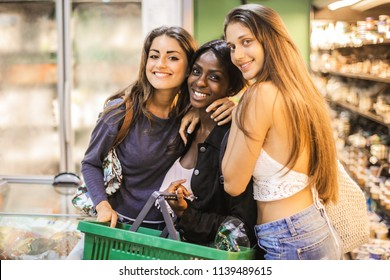 Group of female friends smiling and hugging in a grocery store