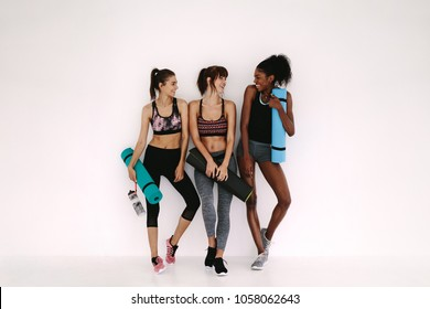 Group of female friends in sportswear smiling together while standing in a gym after yoga workout. Women standing by a wall with exercise mat.
