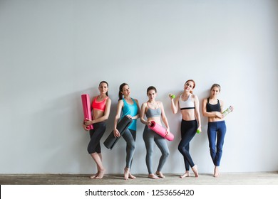Group of female friends in sportswear together standing in a gym after yoga workout.