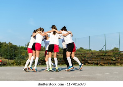 Group of female handball team is rejoicing and celebrating by hugging.
