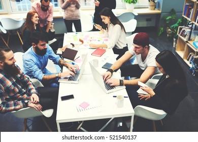 Gruppo di professionisti IT femminili e maschili che lavorano sullo sviluppo di software utilizzando dispositivi moderni mentre si è seduti a tavola. I blogger qualificati sono copywriting per la digitazione di pagine web multimediali sulla tastiera del computer