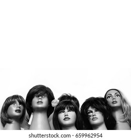 Group of female mannequin heads In the wigs. Black and white retro photo.Hairdresser concept.