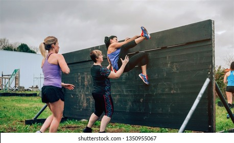 Group of female participants in an obstacle course climbing a wall