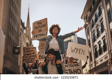 Group of female protesters marching on the road with signboards and smiling. Women holding protest banners and marching outdoors.