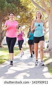 Group Of Female Runners Exercising On Suburban Street