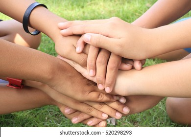 The group of female student with hands in stack, strong concept about teamwork and cooperation, also refers to immigration and friendship.