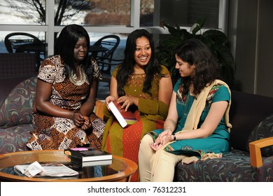 Group of female students dressed in traditional garments reading textbook