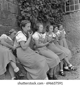Group of female students in school uniforms eating together