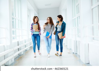 Group of female students walking along the corridor at college