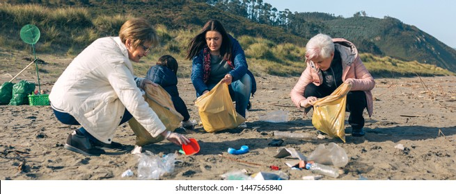 Group of female volunteers picking up trash on the beach