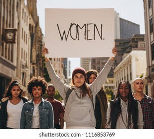 Group of females protesters marching on the road with signboard of women. Woman holding a protest sign about women empowerment with group of females around.