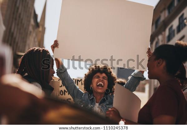 Gruppe der Weibchen, die mit einem leeren Banner draußen auf der Straße protestieren. Weibchen, die während eines Protestes leere Zeichenbrett halten.