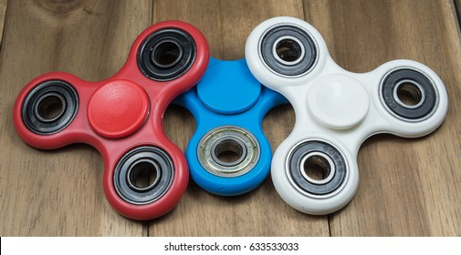 Group of fidget spinner stress relieving toy on wooden background