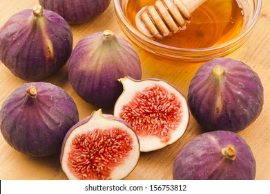 Group of figs with a bowl of honey in the background