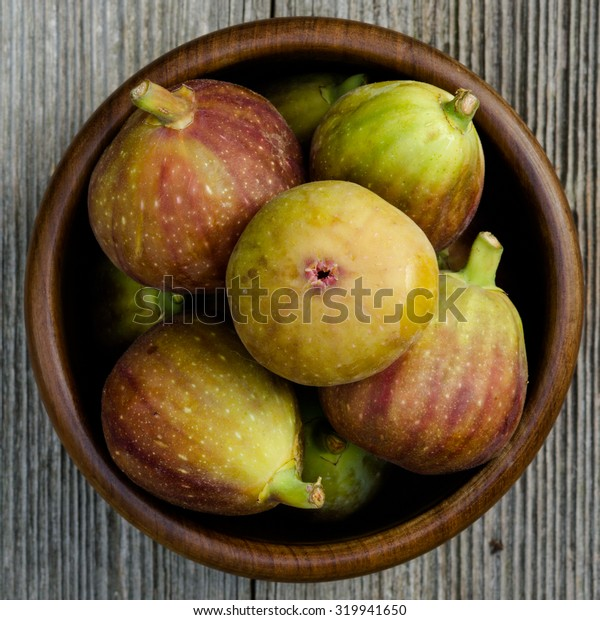 group of figs in a bowl - rustic wooden table, top view