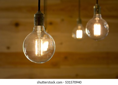 Group of filament light bulbs over a wooden background.