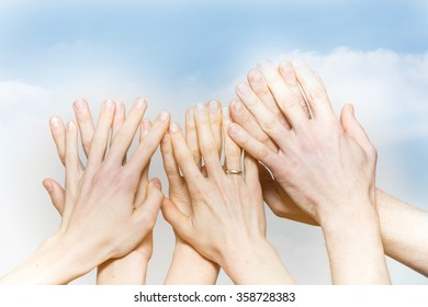 Group fingers of different hands against the sky filtered
