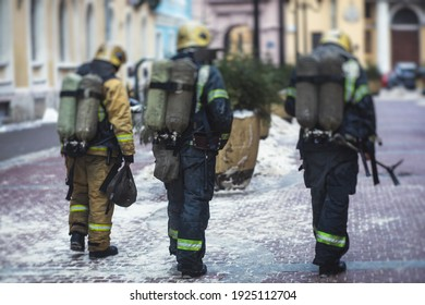 Group of fire men in uniform during fire fighting operation in the city streets, firefighters with the fire engine truck fighting vehicle in the background, emergency and rescue