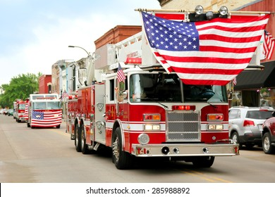A group of fire trucks with American flags on them drive down the road in a small town American Parade during a festival event.