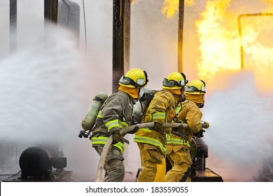 Group of firefighters advance forward putting out a fire.