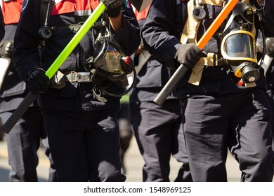 a group of firemen walking in a parade holding in their hands axes and special fireman equipment, blue firemen suits